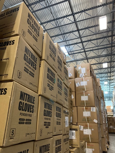 Boxes of nitrile gloves are stacked together, to be delivered through the Protecting Our People initiative