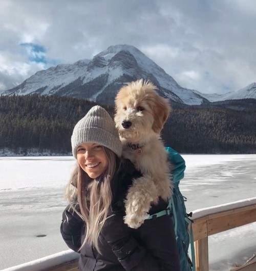 Katelyn Lutes, carrying her dog on her back, with mountain scenery in the background