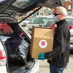 Man loads box of donated food into the trunk of a car.