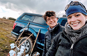 Two researchers posed in front of their truck in a farm field.