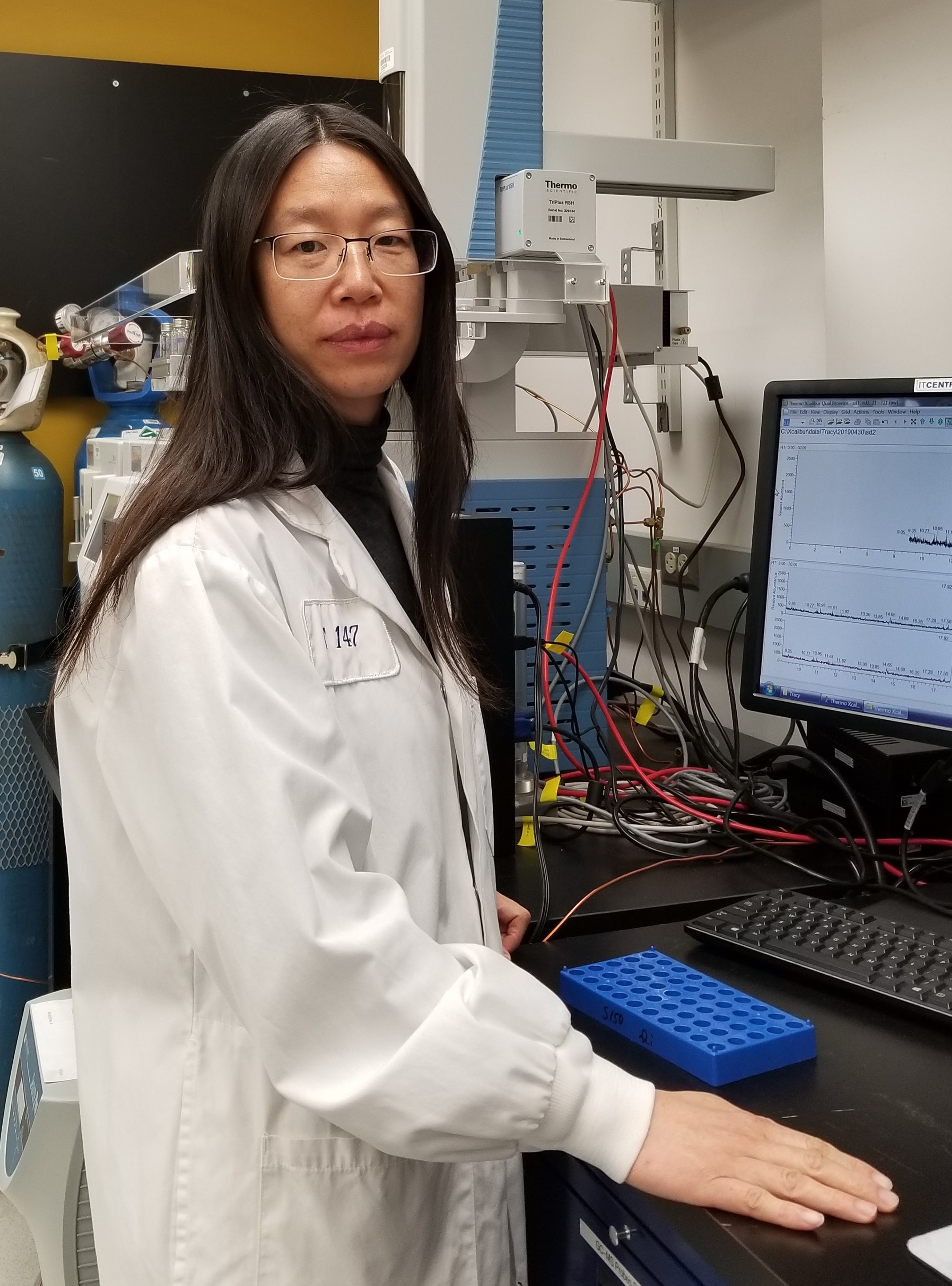 Dr. Suqin Shao standing at a computer in her laboratory